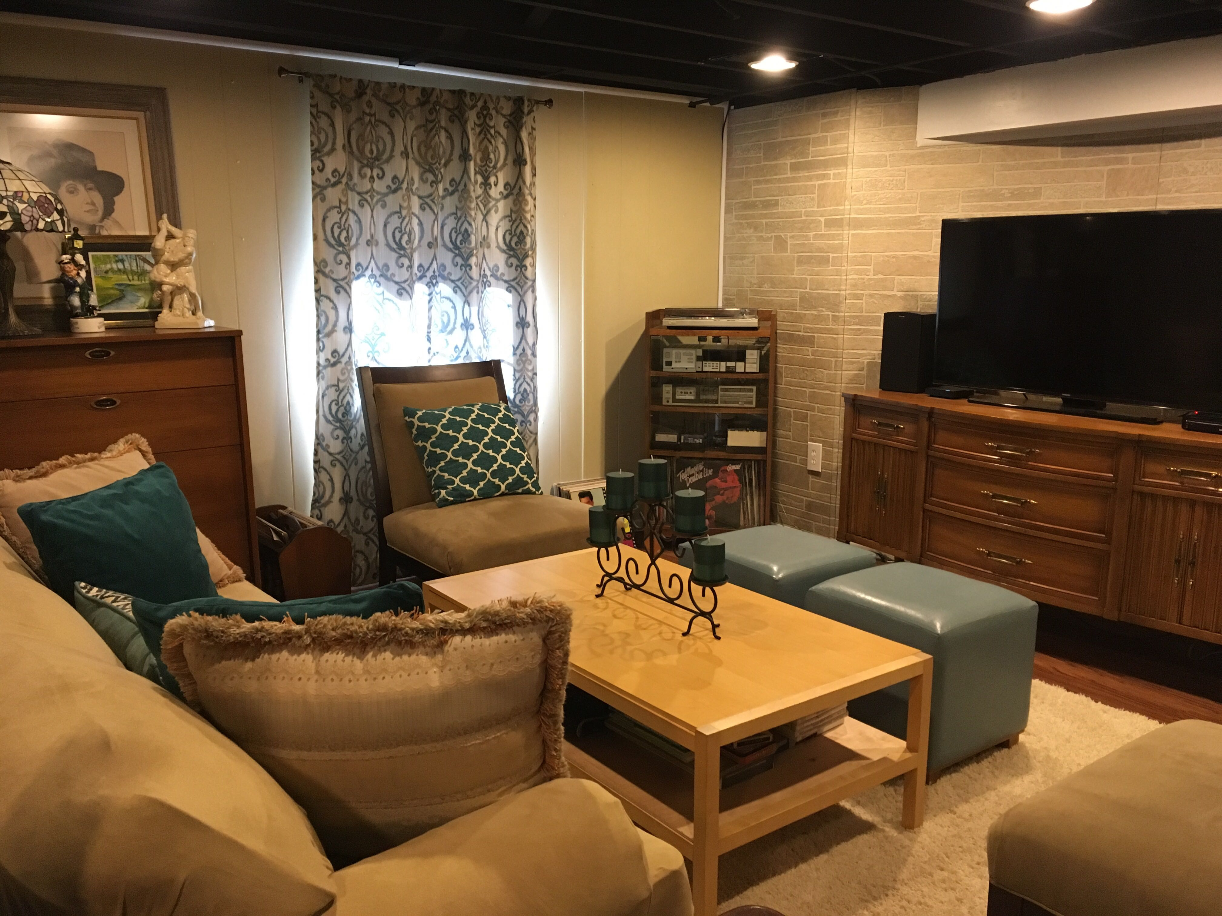 Showcasing a basement/living area remodel with new furniture, paint, and indoor décor.