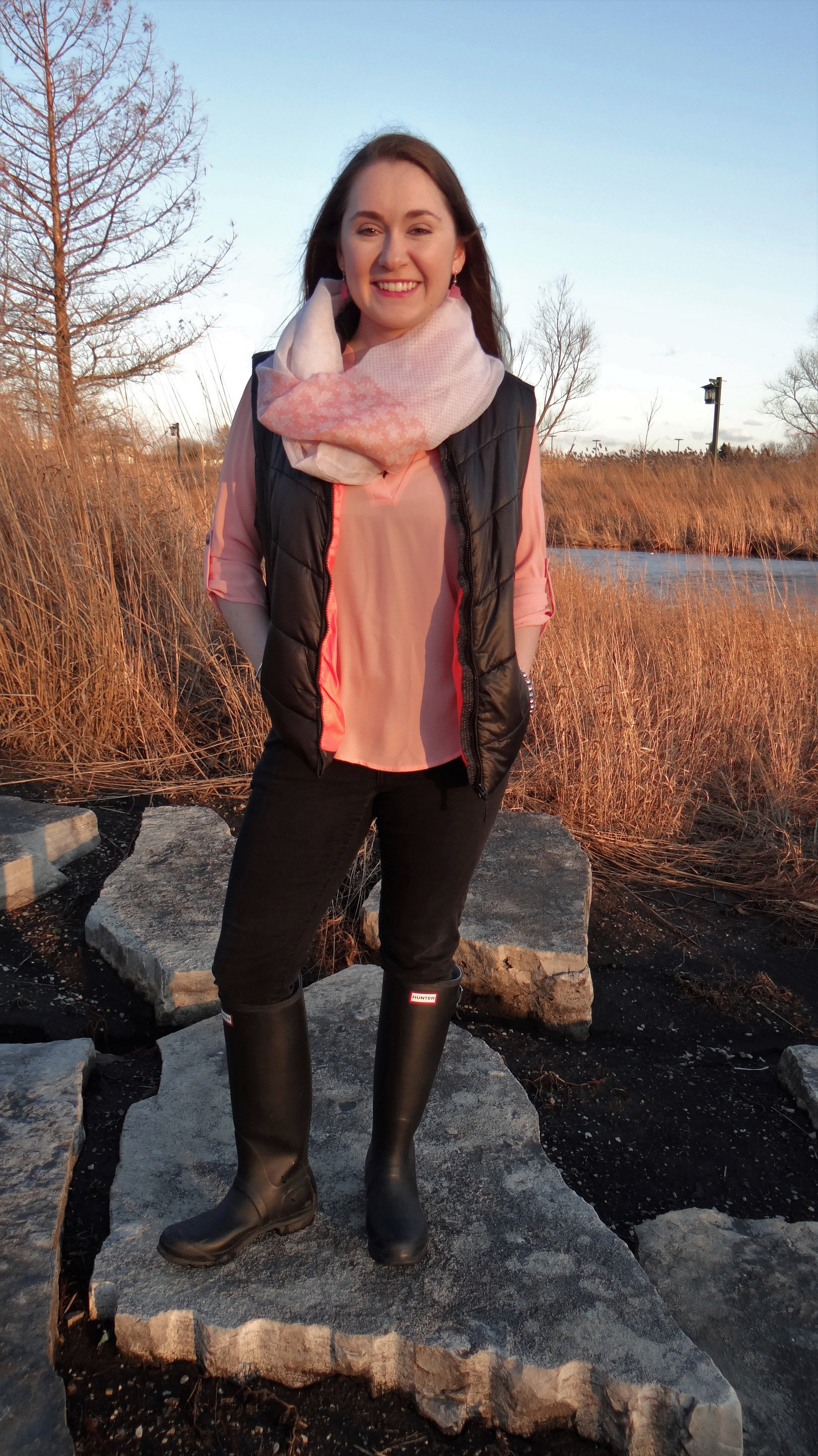 Model is wearing a pink shirt under a pink and black vest with black jeans and boots and silver accessories.
