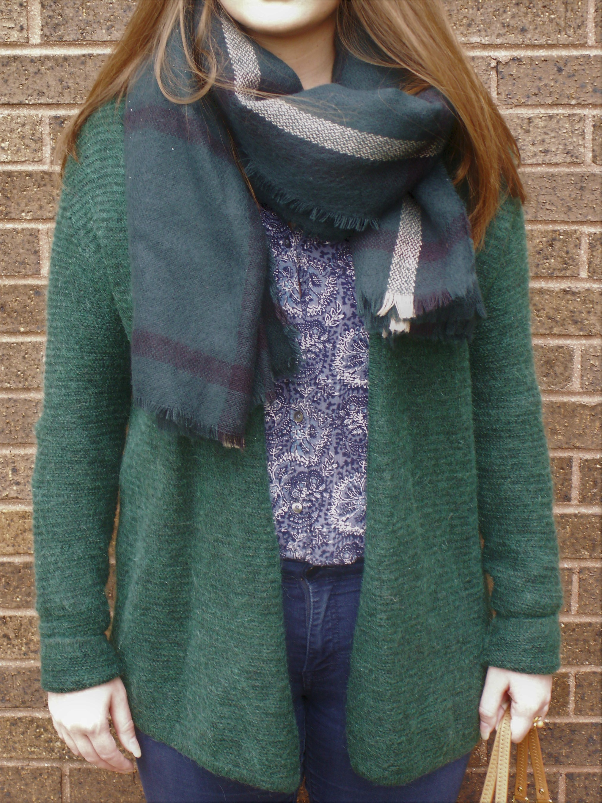 Model is wearing an emerald green cardigan over a sapphire blue paisley shirt with a matching plaid scarf.