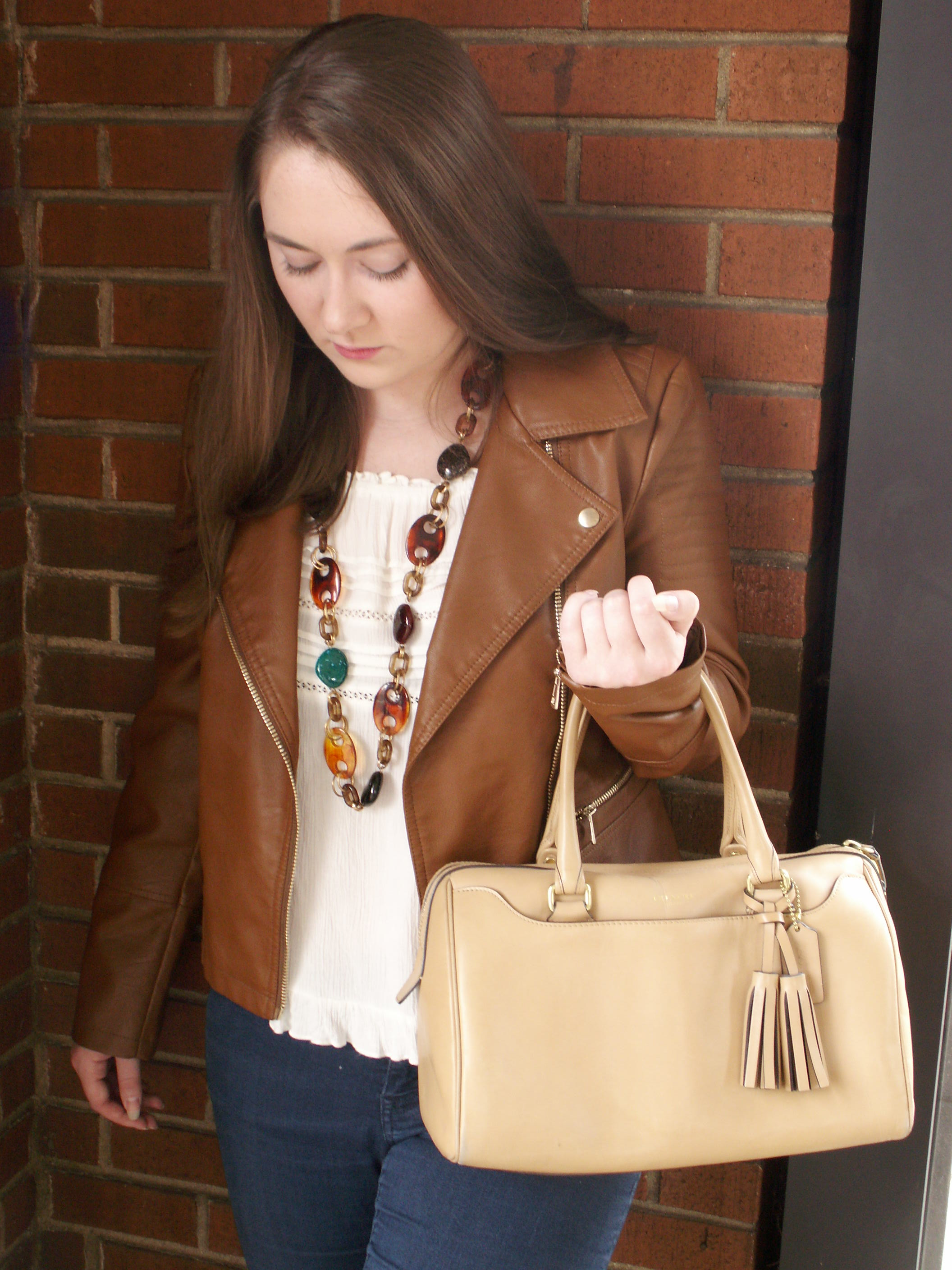 Model is wearing a cognac leather jacket with a white blouse, blue jeans, and leather accessories.