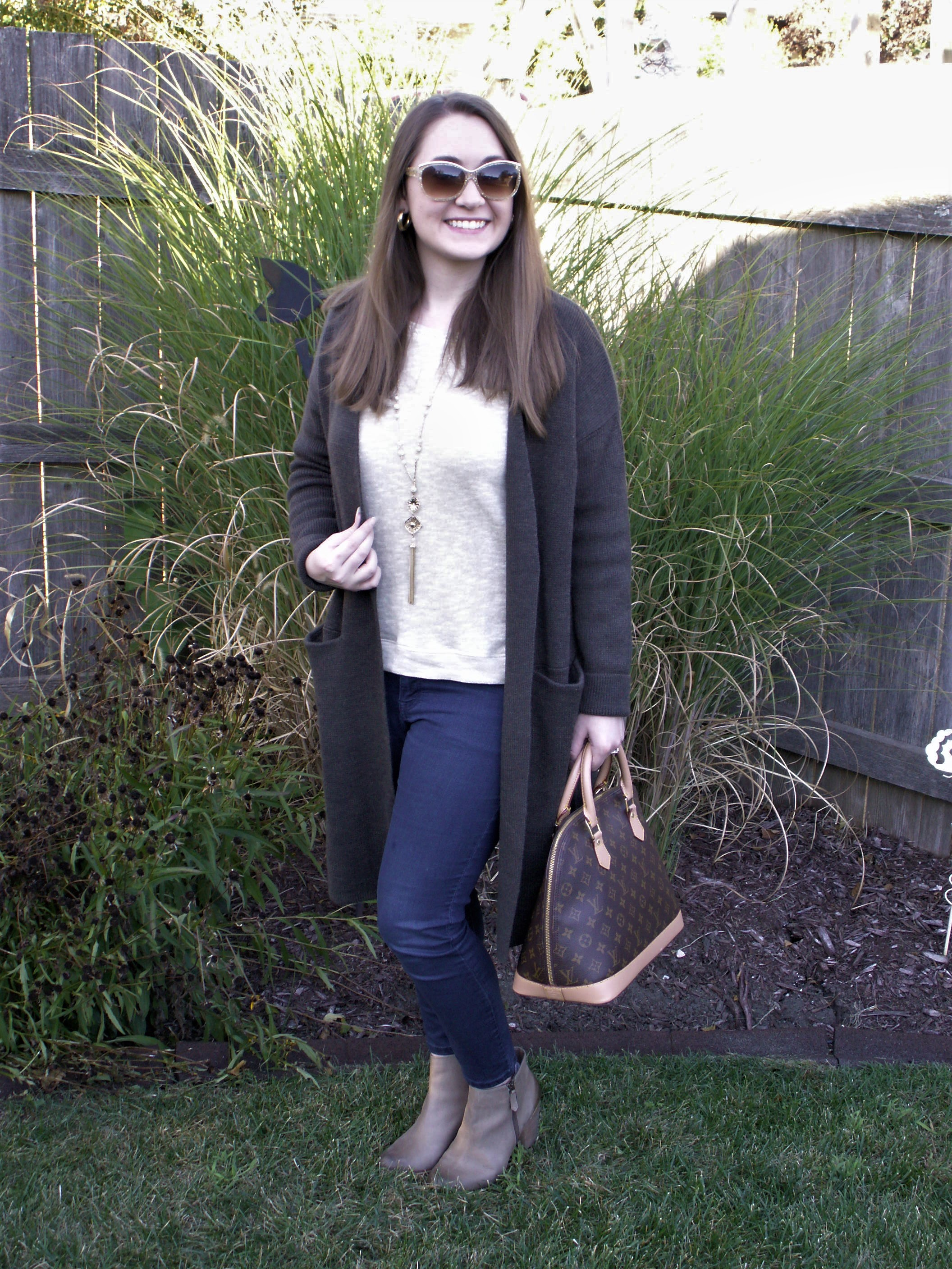 Model is wearing an oversize cardigan over a sweater with a long necklace and ankle boots.